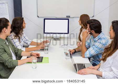 Business team looking at computer screen in the meeting room at office