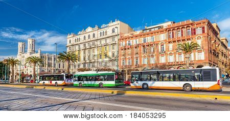 Cagliari, Sardinia - January 2016, Italy: Beautiful colorful buildings on Cagliari seafront, buses and trolley car parked near bus stop on the central street of the city