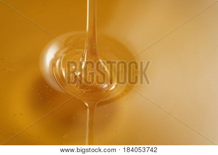closeup of pouring organic honey, amber golden color