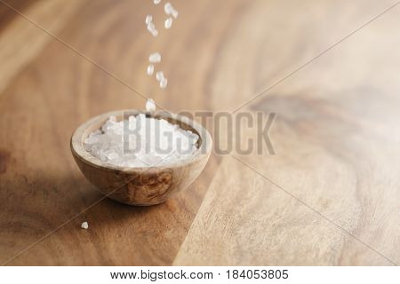 coarse sea salt falling into wooden bowl on table, with copy space