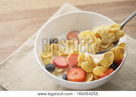 spoon with healthy breakfast with corn flakes and berries, slightly toned photo