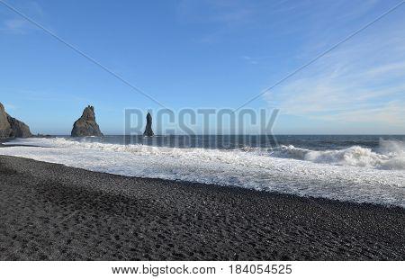reynisdrangar sea stacks off the shore of Reynisfjara beach in Vik Iceland.