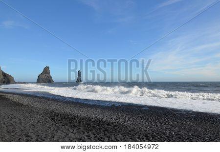 Reynisdrangar sea stacks along the black sand beach in Vik Iceland.