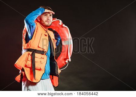 Lifeguard in life vest jacket with ring buoy lifebuoy. Man supervising swimming pool water looking out in the distance on black. Accident prevention.