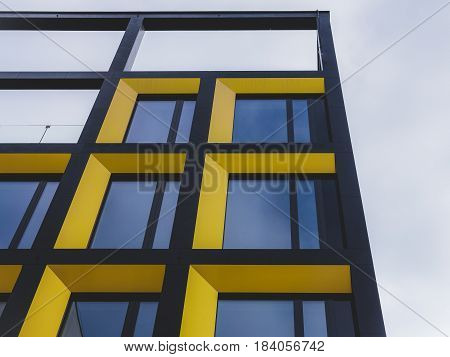 Apartment block with colourful facade in yellow and black.