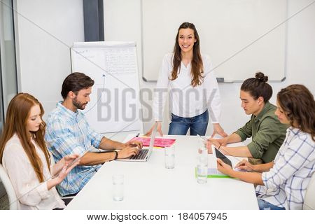 Attentive executive using laptop and digital tablet in conference room at office