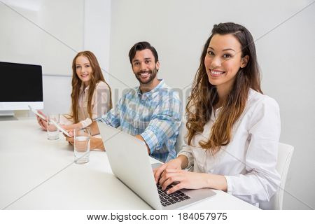 Portrait of executive using laptop and digital tablet in conference room at office
