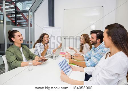 Smiling executive interacting during meeting in conference room at office