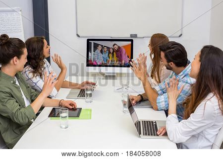 Business team having video conference with another business team in conference room