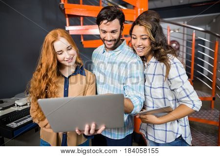 Happy male and female executives using laptop in office