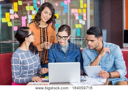 Graphic designers discussing over laptop in office