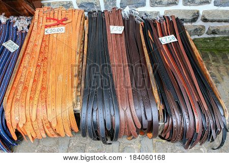 Many different belts for trousers lying on marketplace