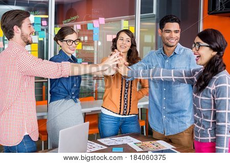 Team of happy graphic designers giving high five in office