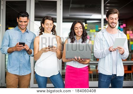 Smiling executives using mobile phone, laptop and digital tablet in office