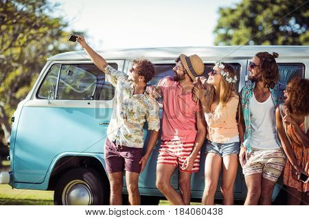 Group of friends taking selfie from mobile phone in park