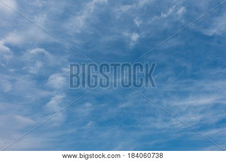 Blue sky with translucent watercolor-like clouds at daytime