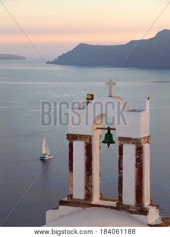 Greek Orthodox Church Bell Tower against Aegean Sea with Sailing Boat at the Sunset, Santorini, Greece