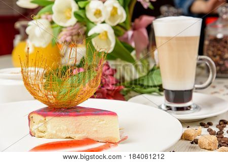 Horizontal studio shot of a coffee cup with berry cheesecake and caramel decoration.