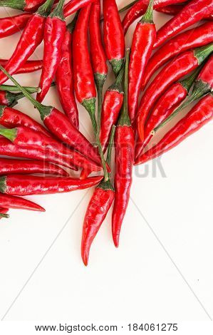 red hot chili peppers, popular spices concept - beautiful handful of plenty red hot pepper in bulk, pods scattered on white background, top view, flat lay, vertical with free space for your text