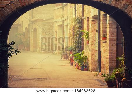 Narrow street of medieval San Quirico d'Orcia city with arch, green plants and cobblestone, travel foggy morning Italy background. Vintage hipster style.