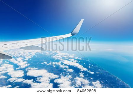 wing of an airplane flying high in the sky above the clouds