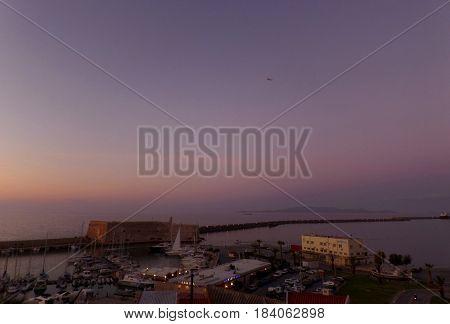 Breathtaking evening purple sky over the old port of Heraklion, Crete island, Greece