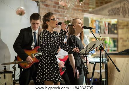 Music band of four people (two women, two men) performs on stage, focus on left woman