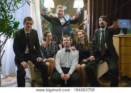Music band of six people (two women, four men) poses on armchairs in club