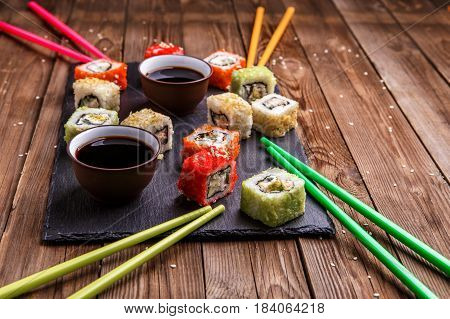 Photo of rolls, multi-colored sticks, soy sauce on wooden background