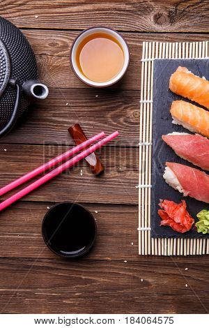 Photo of sushi, red sticks, soy sauce on wooden table