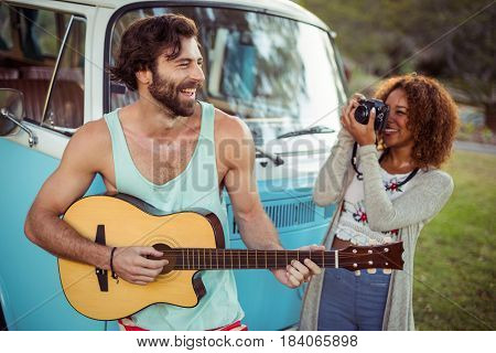Man playing guitar while woman photographing with camera at music festival