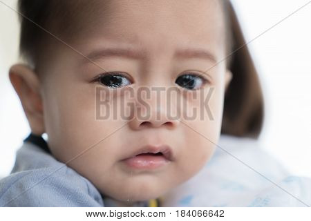 Asian 5 months baby boy crying in mother arm.