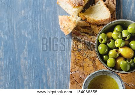 Olivier Oil With Fresh Herbs And Bread. Blue Background. Italian