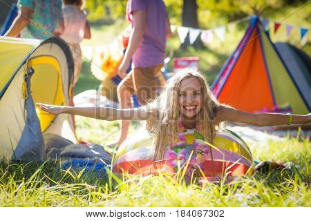 Portrait of woman leaning on beach ball at campsite on a sunny day