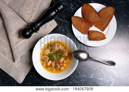 Bean Soup In White Plate With Metal Spoon, Several Toast On White Plate On A Black Stone Background.