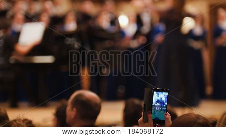 Spectators at concert - people shooting performance on smartphone, music opera, telephoto