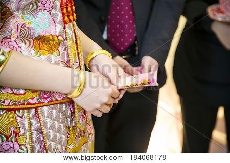 The bride wears the luxury  dragon and phoenix bracelets and receives the pockey money, which represent a blessing to her marriage, from the relatives