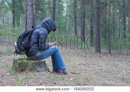 A woman sits on a stump in the woods early in the morning and checks her cellphone. A female hiker backpacker trekking in the woods and mountains. Healthy lifestyle adventure camping on hiking trip.