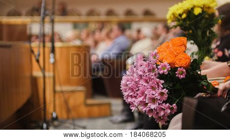 Audience in the concert hall holding flowers for artists on stage telephoto