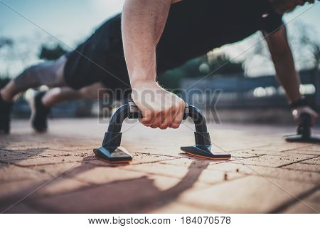 Closeup view of Handsome sport man doing pushups in the park on the sunny morning.Healthy lifestyle concept.Training outdoors.Blurred background