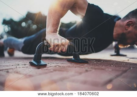 Healthy workout lifestyle concept.Training outdoors.Handsome sport athlete man doing pushups in the park on the sunny morning. Blurred background