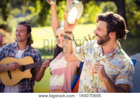 Man holding beer bottle and playing tambourine at campsite on a sunny day