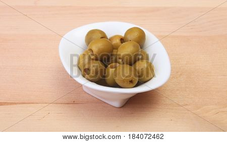 Bowl with fresh olives on wooden background