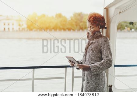 Attractive smiling mixed girl is standing on the deck of a ship with digital tablet cute black teenage female with curly afro hair holding touch pad while standing on seafront with copy space
