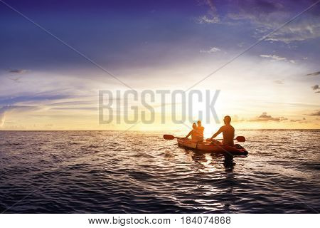 Travel concept with family swimming in sea on kyak at sunset backdrop. Space for text