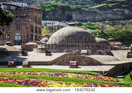 View of the dome of the ancient sulfur baths in Tbilisi in the foreground a bright flower bed. April 17 2015