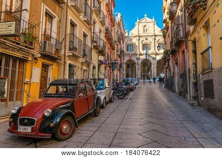 Cagliari - January 2 of 2016, Sardinia, Italy: Street view with old houses, Church and Vestry of Saint Michele and vintage red car on Via Domenico Alberto Azuni