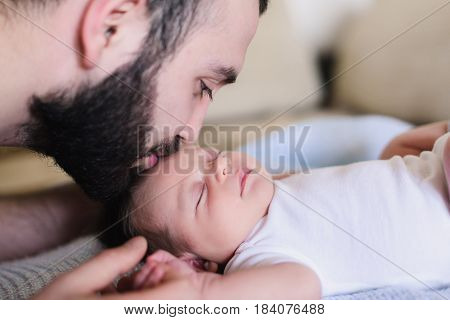 A young father kisses his sleeping newborn son. Father and newborn baby closeup. Father and newborn lying on the bed.