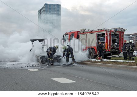 RIGA LATVIA - APRIL 11 2014: Out into the road burning car. Firefighters have arrived. Going on fire extinguishing works. Traffic is stopped.