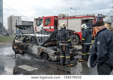 RIGA LATVIA - APRIL 11 2014: Out into the road stands just doused car. Firefighters inspected losses.